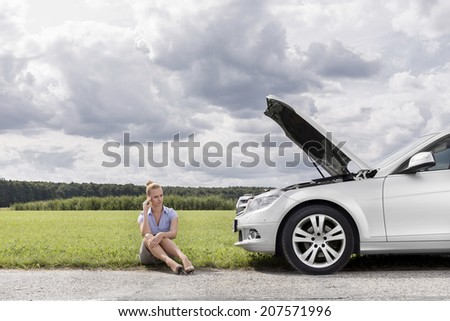 Full length of worried businesswoman sitting by broken down car at countryside - stock photo