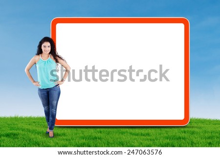 Full length of young asian woman with casual clothes, standing next to empty billboard at field - stock photo