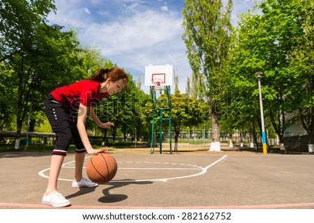 Full Length of Young Athletic Woman Dribbling Basketball at Mid Court in Lush Green Park with Backboard and Basket in Background - stock photo