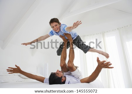 Full length of young boy balancing on father's legs in bedroom - stock photo