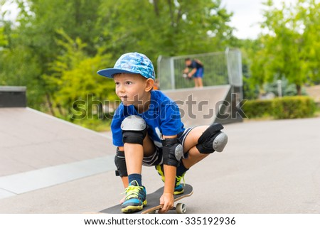 Full Length of Young Boy Riding Skateboard in Crouched Position in Skate Park with Ramp in Background - Looking Focused and Concentrating - stock photo