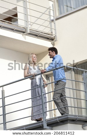 Full length of young business couple conversing at hotel balcony - stock photo