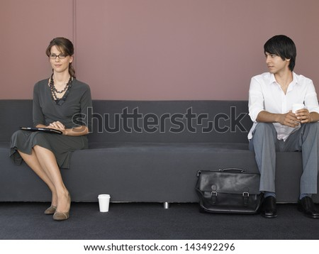 Full length of young businessman and businessman sitting on sofa in waiting room - stock photo