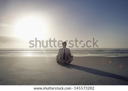 Full length of young businessman meditating in lotus position on beach - stock photo