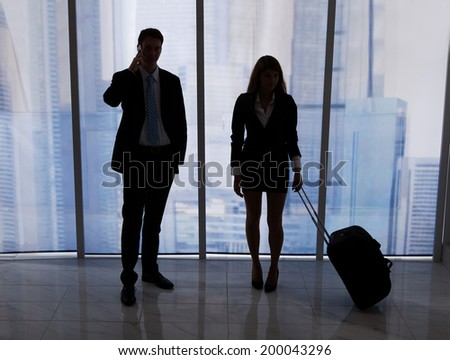 Full length of young businessman on call standing by female colleague with luggage in office - stock photo
