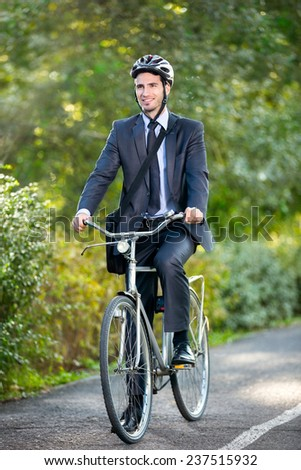 Full length of young businessman riding a bicycle to work - stock photo