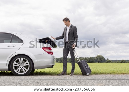 Full length of young businessman unloading luggage from broken down car at countryside - stock photo