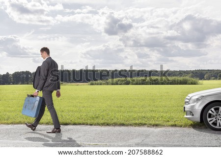 Full length of young businessman with gas can leaving broken down car at countryside - stock photo