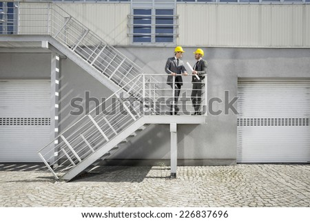 Full length of young businessmen with blueprint discussing on stairway - stock photo