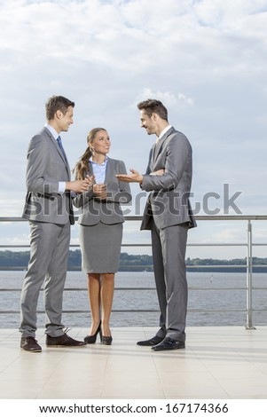 Full length of young businesspeople communicating on terrace against sky