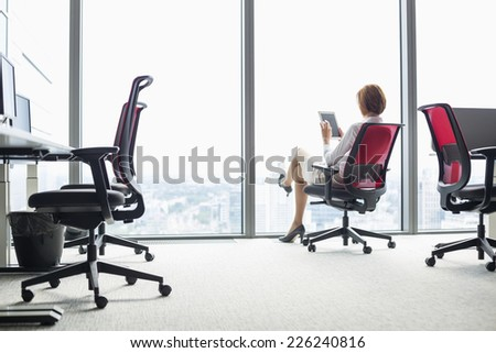Full length of young businesswoman using tablet PC on chair in office