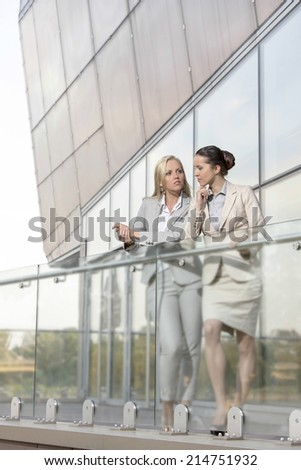 Full length of young businesswomen conversing at office balcony - stock photo