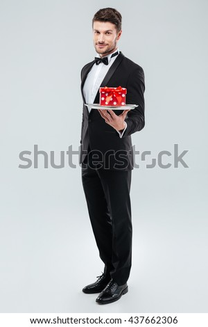 Full length of young butler in tuxedo standing and holding tray with gift box - stock photo