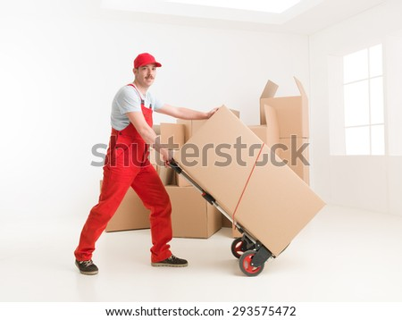 full length of young caucasian deliveryman with hand truck, transporting cardboard boxes. moving house - stock photo