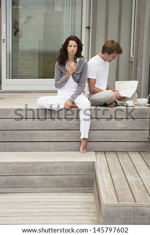 Full length of young couple having breakfast on porch
