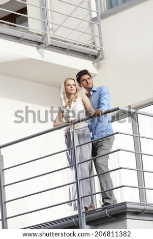 Full length of young couple looking away while standing at hotel balcony - stock photo
