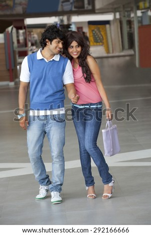 Full length of young couple together in shopping mall - stock photo