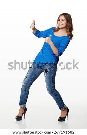 Full length of young cute smiling emotional girl giving you double thumbs up over white background - stock photo