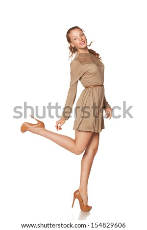 Full length of young elegant redheaded female in dress, smiling, over white background - stock photo