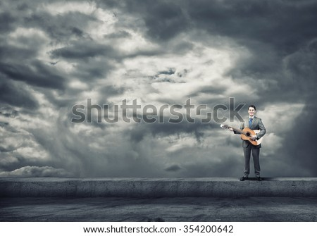 Full length of young excited businessman playing acoustic guitar on cloud background