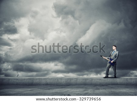 Full length of young excited businessman playing guitar on cloud background