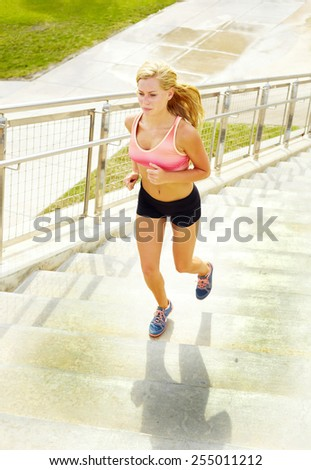 Full length of young female athlete jogging on steps - stock photo