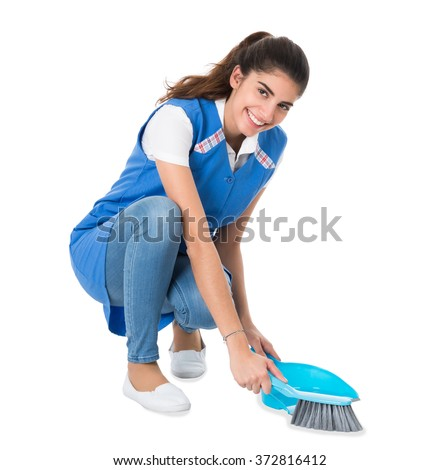 Full length of young female cleaner sweeping with small broom and dustpan on white background - stock photo