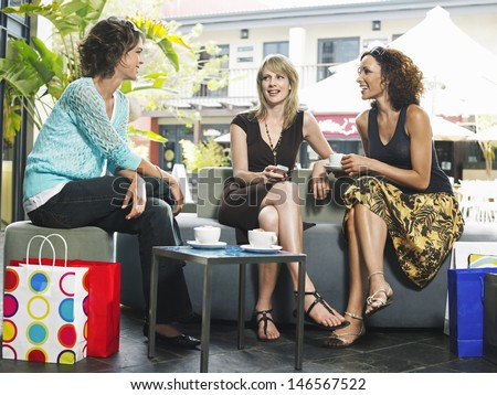 Full length of young female friends gossiping at outdoor cafe - stock photo