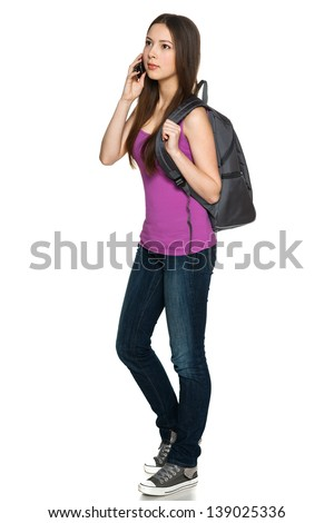 Full length of young female with backpack talking on cellphone while looking away, against white background - stock photo