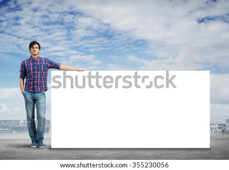 Full length of young handsome man with blank banner - stock photo