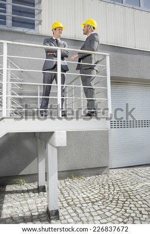 Full length of young male engineers discussing on stairway - stock photo