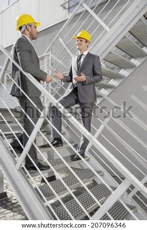 Full length of young male engineers discussing on steps - stock photo