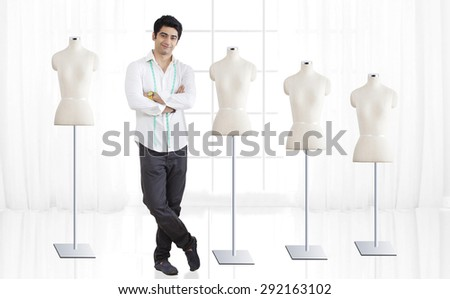 Full length of young male fashion designer standing by mannequin at studio - stock photo