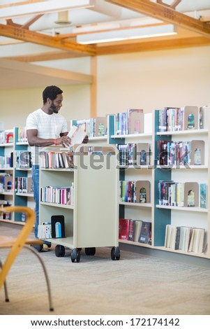 Full length of young male librarian with trolley arranging books in library - stock photo