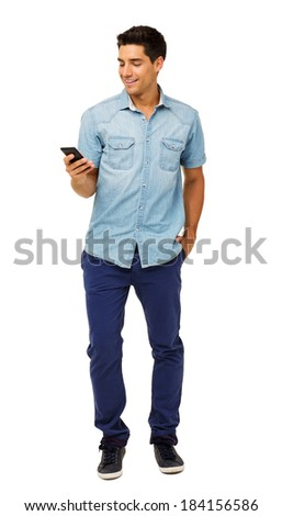 Full length of young man reading text message on smart phone against white background. Vertical shot. - stock photo