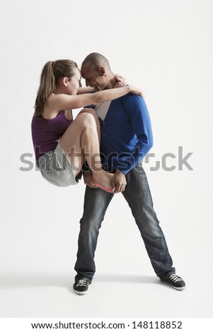 Full length of young man supports modern dance partner over white background