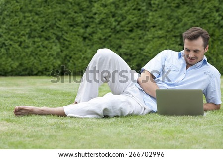 Full length of young man using laptop while lying on grass in park - stock photo