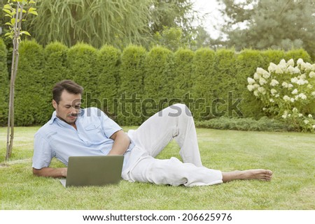 Full length of young man using laptop while reclining in park - stock photo