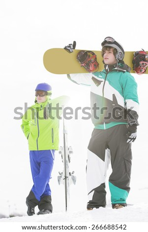 Full length of young men with snowboards in snow - stock photo