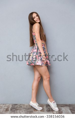 Full length of young pretty happy cheerful charming female in summer floral top and skirt with long hair posing over gray background - stock photo