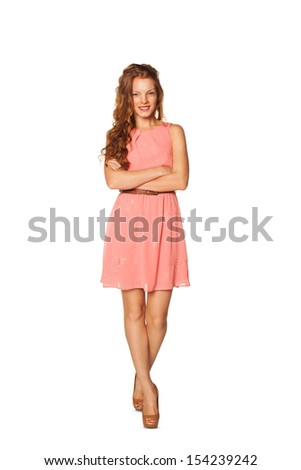 Full length of young redhead female smiling and embracing herself against a white background - stock photo