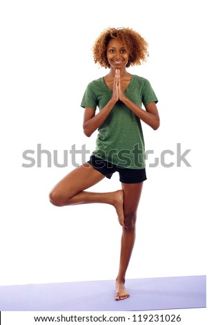 Full length of young smiling black woman doing yoga exercise isolated over white background - stock photo