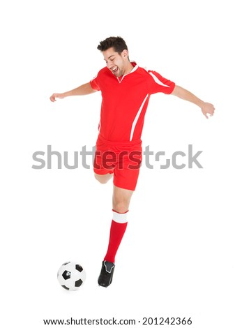 Full length of young soccer player kicking football over white background - stock photo