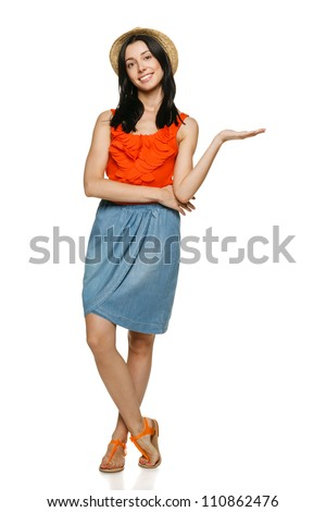 Full length of young trendy woman showing a product - empty copy space on the open hand palm, over white background