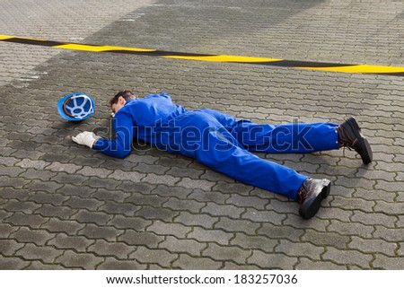 Full length of young unconscious technician lying on street - stock photo