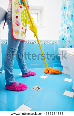 Full length of young woman cleaning ceramic floor of bathroom at home by mop - stock photo