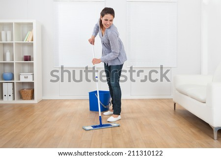 Full length of young woman cleaning hardwood floor of living room at home - stock photo