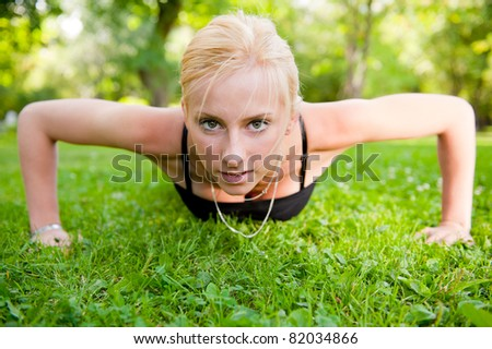 Full length of young woman doing pushups on green grass at summer park - stock photo