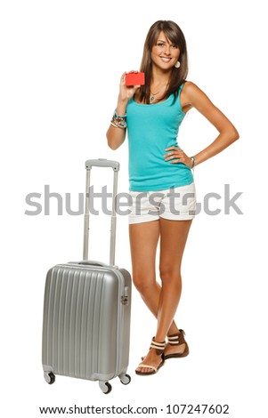 Full length of young woman in casual standing with silver travel bag holding empty credit card, isolated on white background