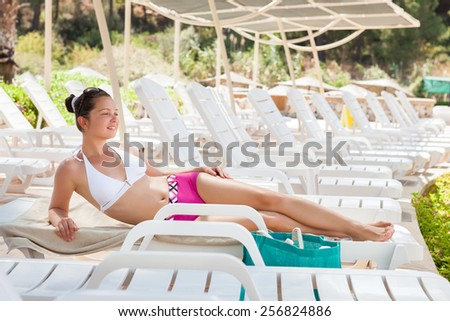 Full length of young woman in swimwear relaxing on lounge chair at resort - stock photo